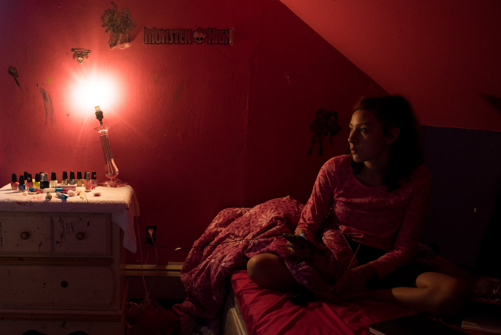 """6/29/16 – East Hartford, CT – Yaritza watches TV in her room at Maritza's house in East Hartford on Wednesday, Jun. 29, 2016. (Photo by Nicholas Pfosi)I met Christian during his graduation from East Hartford High School where he was wheeled across the stage by two paramedics on a stretcher. Christian was diagnosed with mitochondrial disease, an extremely rare genetic disorder that, due to complications because of the disorder, has left him ventilator-dependent and bed-ridden. Christian is one of five children who Maritza Vega raises. Two of her other children, Roberto """"Macho"""" Rodriguez, 5, and Trinidad Rodriguez, 10, both have been diagnosed with autism. Yaritza Rodriguez, 12, the second oldest besides Christian who is 19, suffers from chronic depression, anxiety, PTSD and ADHD. She receives medication but also hurts herself. Marianna Rodriguez, 7, is neurotypical. The children's father, Roberto Rodriguez is in jail for violating probation and will be released in September 2016. He was original in jail and subsequently on probation following a conviction of sexual assault of a minor in 2001. The family visits him about twice a month in prison.Maritza, who doesn't work, gets help from her extended family, most primarily her grandmother, Maria Vega. The family receives Social Security Income and Christian's care is paid for by state insurance. He is tended to by two full-time nurses, Jen Krug, and Romanita Lazu. He is educated by Denise Beaulieu, a special education teacher provided by the state."""