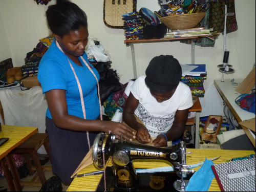 Our trainer guiding Miriam as she sews a round skirt