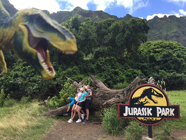Family Pretending To Get Attacked By T-Rex Leaning On Large Fallen Log Mountains In The Background Jurassic Park Sign In The Foreground