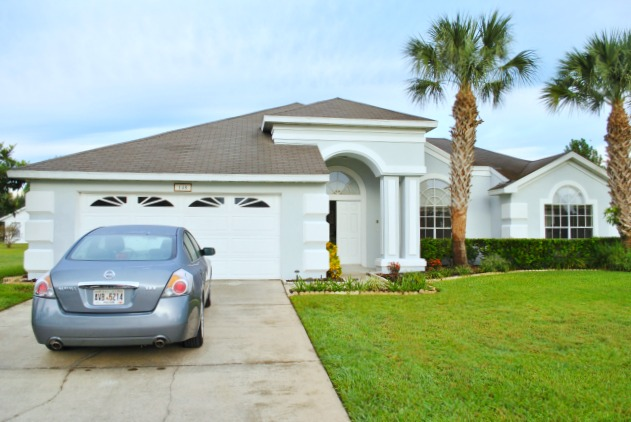 Outside view of a villa in Orlando Florida with palm trees and hire car