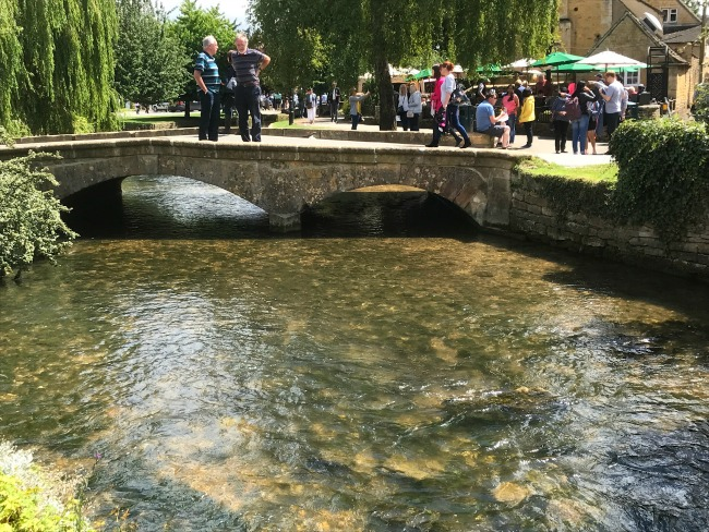 Bourton On The Water Village England Cotswolds With Low Bridges Over The River Sun Shining Small Crowd Of People Under Green Umbrellas