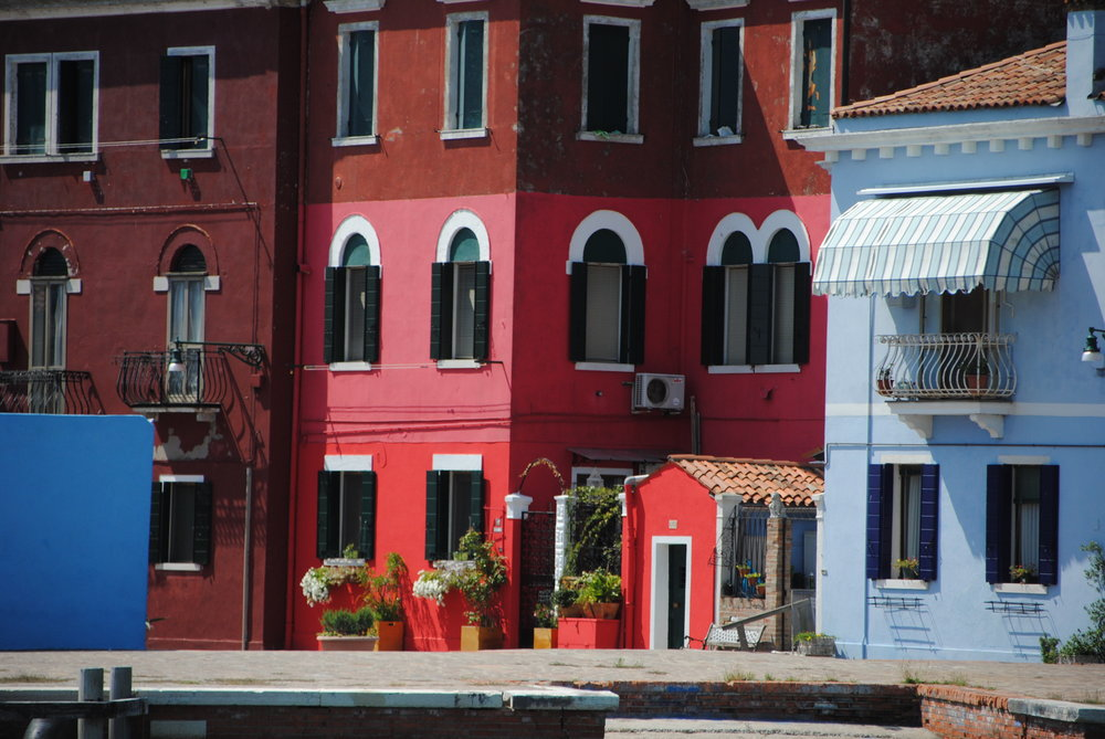 The island of Burano. Pink Red and Blue Houses Lots Of White Flowers In Window Boxes Striped Canopies Shading The Upstairs Windows