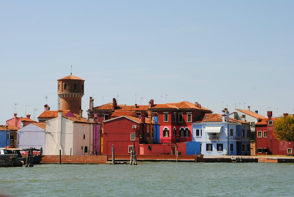 A View Of Burano From The Ferry Boats Moored On The Left Brightly Coloured Blue and Pink Houses In The Front Of The Picture Tower In The Background