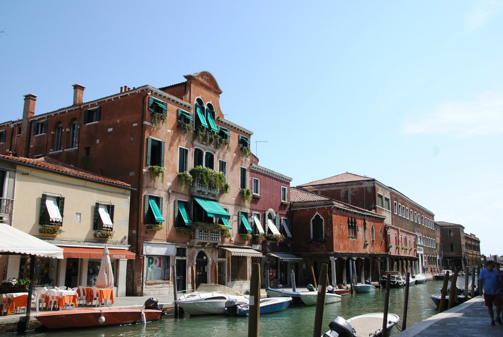 View along canal in Murano. Small restaurant with tables on pavement to the left. Lots of boats tied up along both sides of the canal. Tall building with canopies over each of the windows and ivy trailing from the balcony.