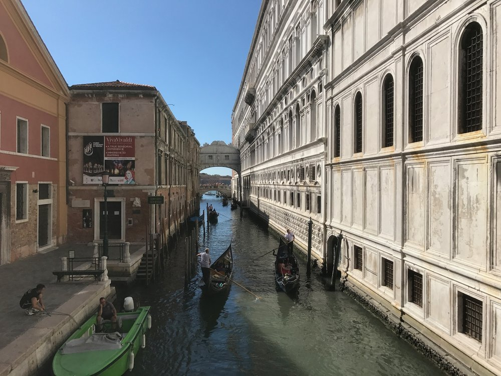 Looking Down One Of The Canals In Venice Towards The Back Of The Bridge Of Sighs With Gondolas Going Past
