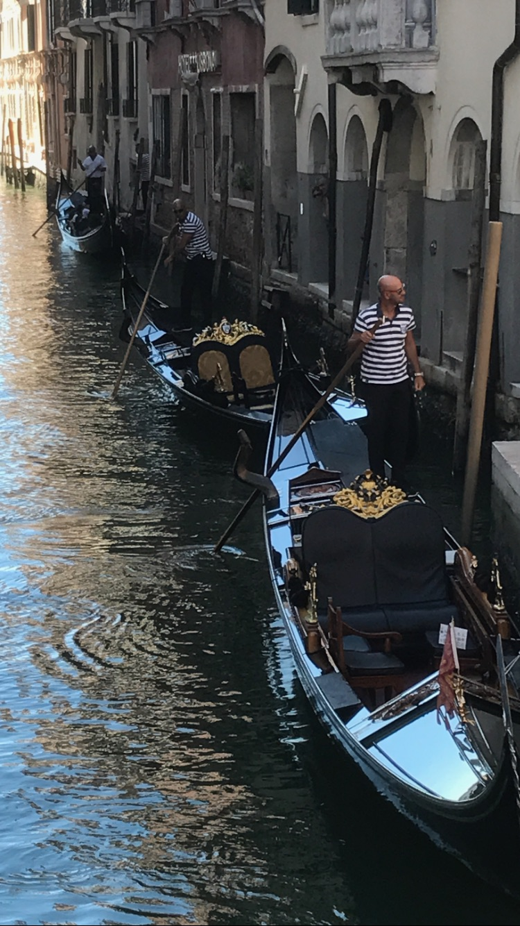 Looking down from a bridge at the queue of gondolas with Gondolier's in their traditional black and white striped tops