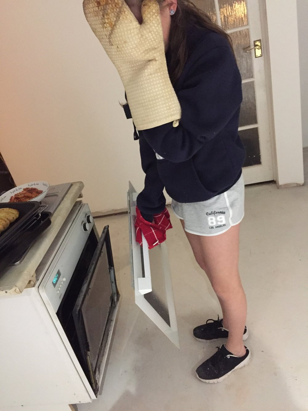 Girl with face covered and oven door in her hand because it had fallen off