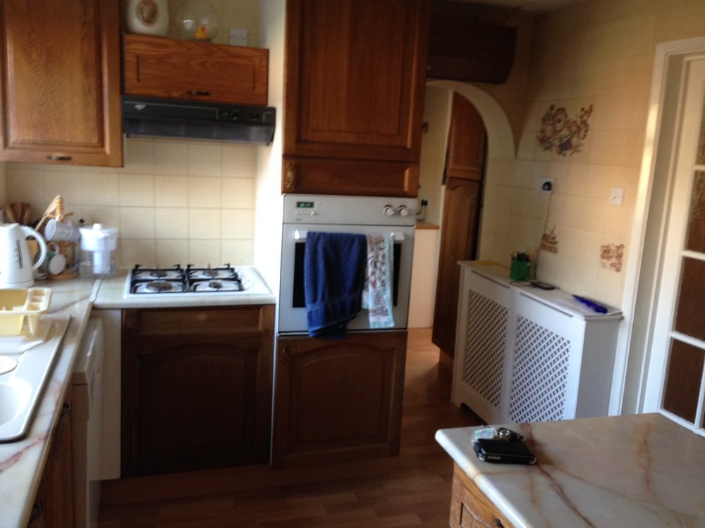 An old kitchen with brown wood cupboard doors and beige and brown tiles all in a very small space.