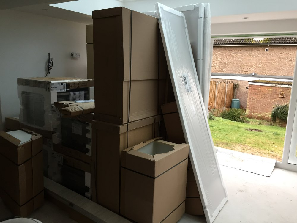 Boxes containing the new kitchen piled up with a view of the garden in the background.