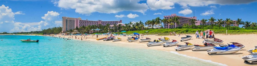 Caribbean beach with bright blue sea, boats on the golden sand and hotels and palm trees in the background