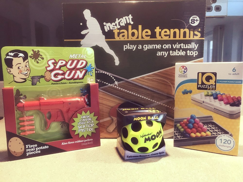 Assortment of toys, red spud gun, yellow moon ball, IQ puzzle, table tennis set