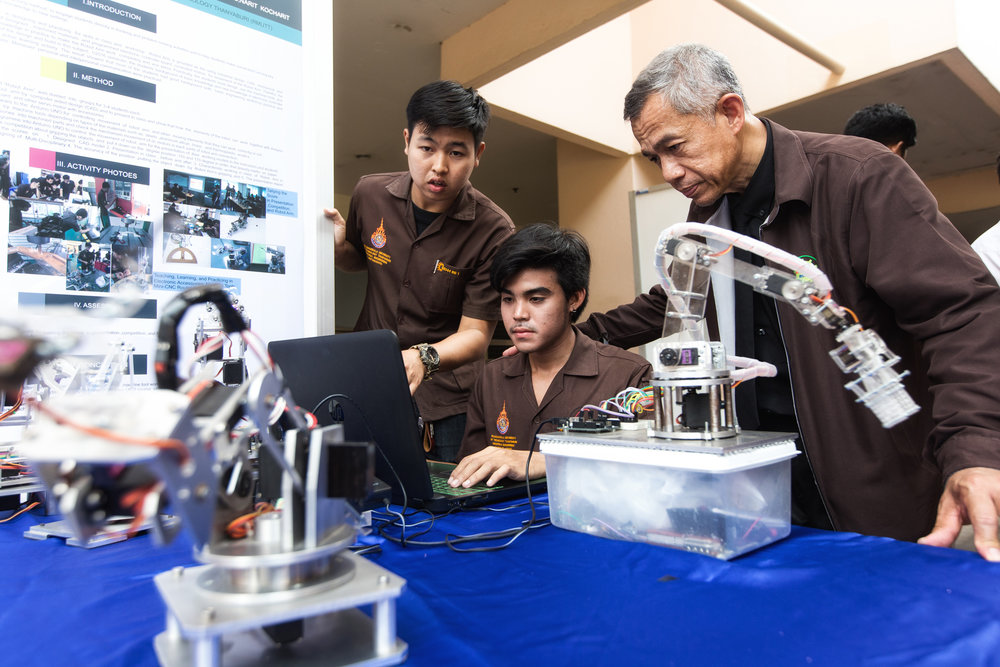 As part of CDIO's active learning, students design and build real-world solutions. Industrial Engineering students Takonkiat Arirob (centre), 23, and Udomsak Wattanagool, 22, carry out a demonstration of the robotic arm they created with supervision from their lecturer Sakchai Chantasri (right), 54.