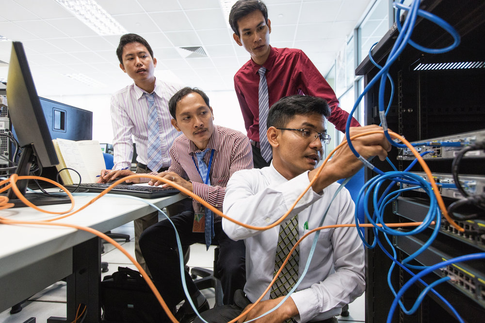 Piseth Keo (right), 27, an information communications teacher from the Koh Kong Provincial Training Centre, Cambodia, setting up a computer network with three TVET participants. They are in the Computer Technology Lab of Singapore's ITE College East.