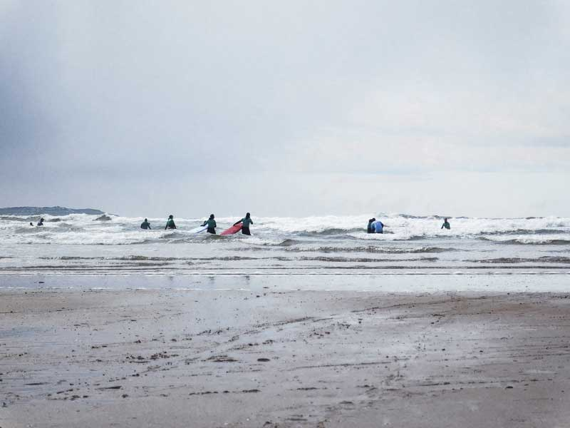 Surfers entering the water in Tullan Strand, Bundoran, Ireland