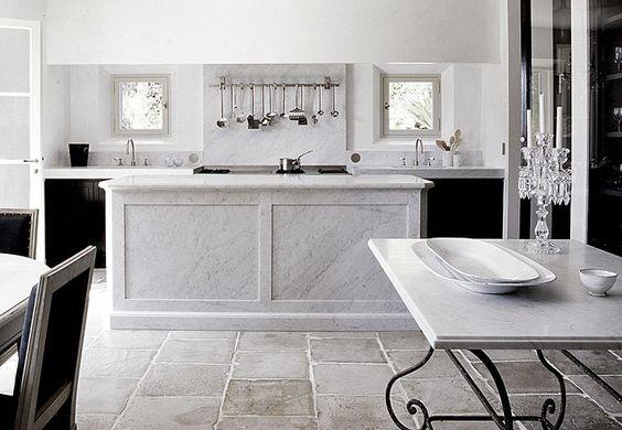 Underbart lantligt kök i fransk anda med rustikt golv i kalksten, köksö, bänkskiva och stänkskydd i Bianco Carrara marmor. Le Mas des Oliviers av Joseph Dirand. Fotografi: Adrien Dirand