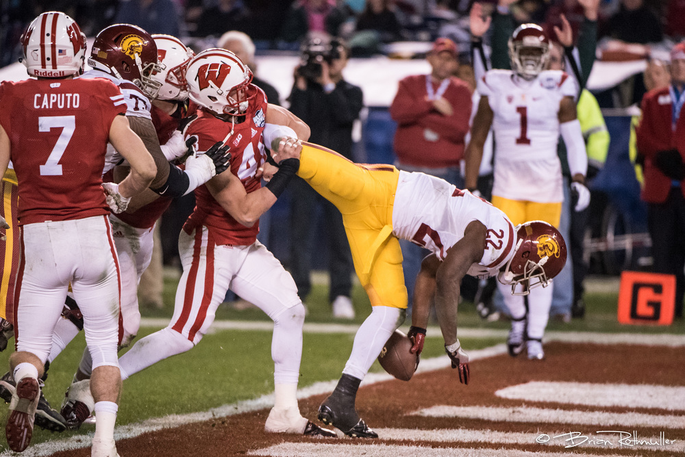 This photo tells a good story. You see the player going in for a touchdown, the ref in the background signaling a touchdown and the goal marker on the right side. It is also enhanced by the fact it looks like the Wisconsin player is trying to break the running back's leg.