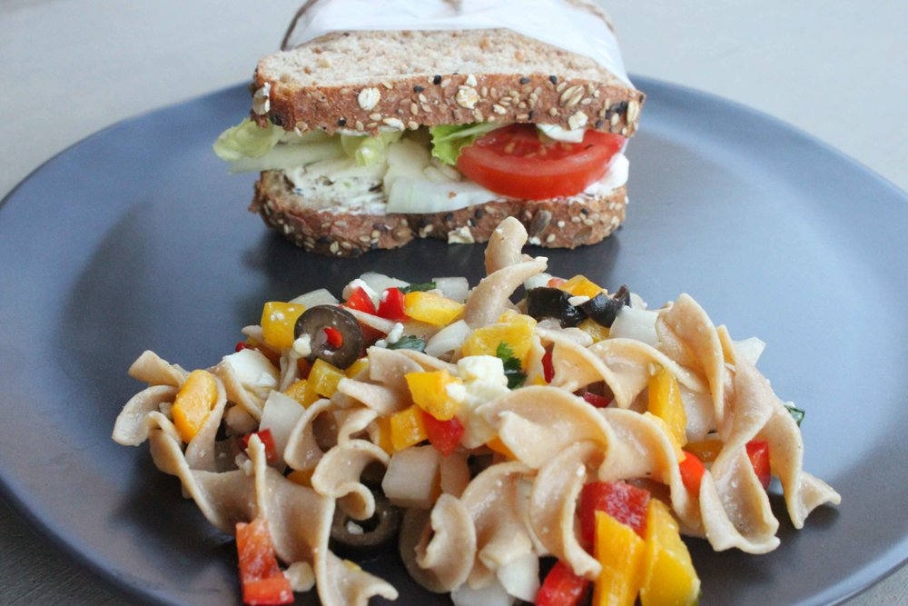a wrapped dill sandwich shown with the AKIM pasta salad.