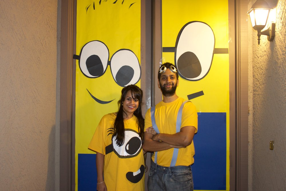 "Standing in front of our #DIY minion doors.  The HUBS wanted to be a ""lumberjack"" Minion 😂. Leave a comment 👇🏽 if you want me to post a tutorial for how to create the HUBS goggles and my minion tshirt.  We DIY'd basically everything at this party haha."