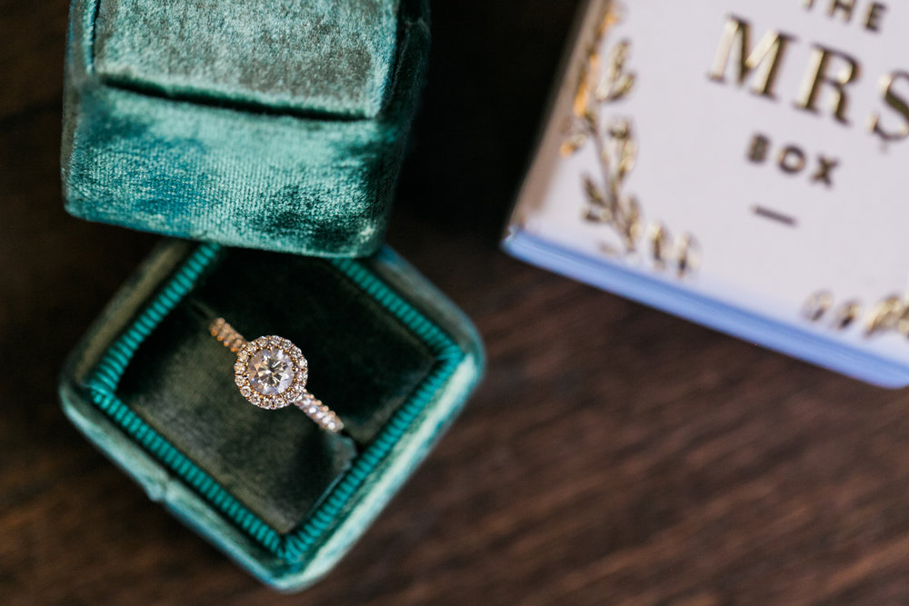 Halo engagement ring in a green Mrs. Box at a destination weddin