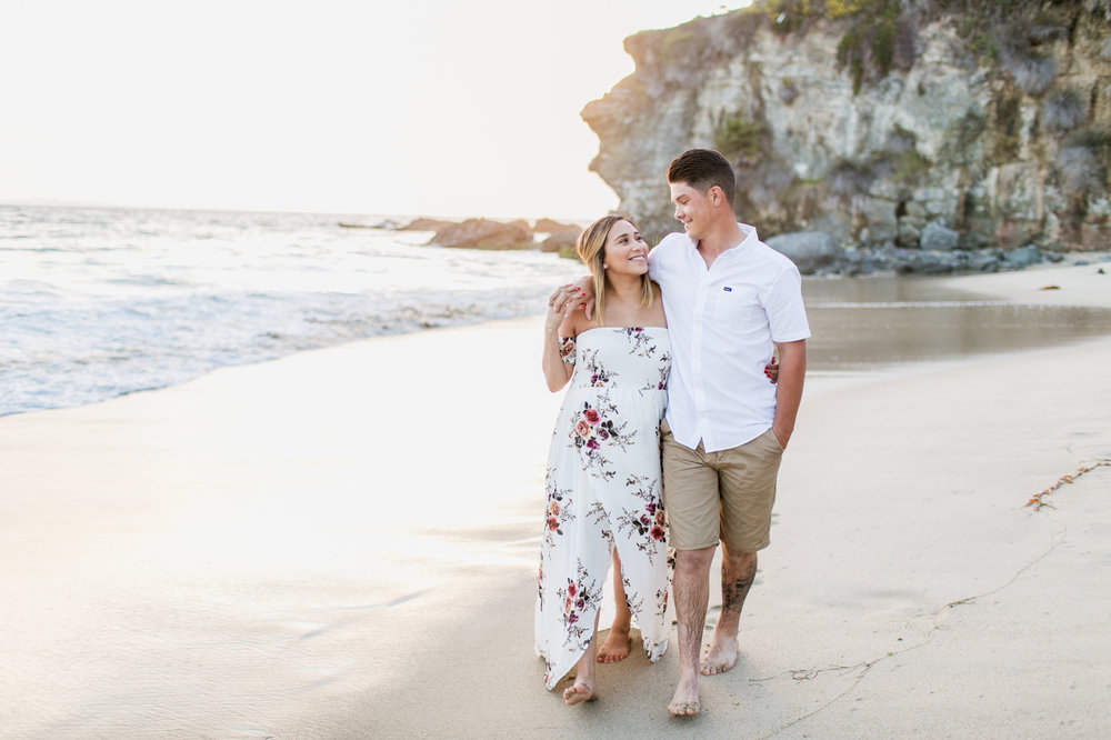 Couple walking on beach during Laguna Beach maternity session at Thousand Steps Beach with photographer Lovisa Photo.