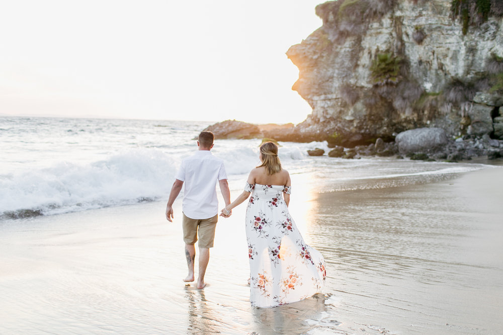 Couple walking towards ocean during Laguna Beach maternity session at Thousand Steps Beach with photographer Lovisa Photo.