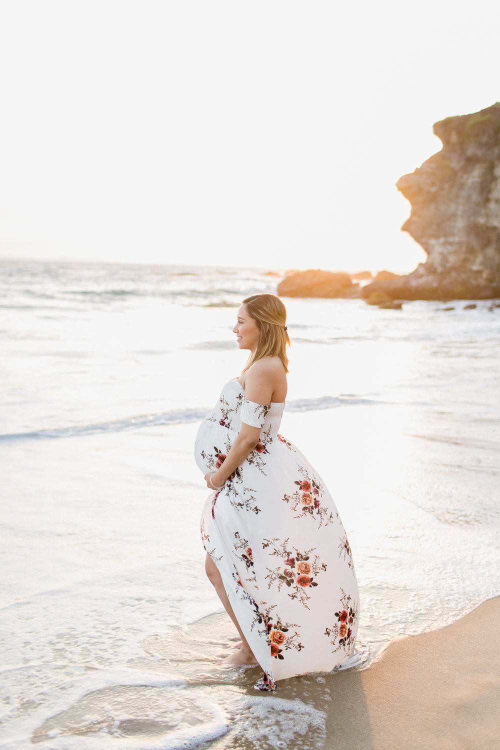 Pregnant mom holds her belly during maternity session at Thousand Steps Beach with Laguna Beach maternity photographer Lovisa Photo.