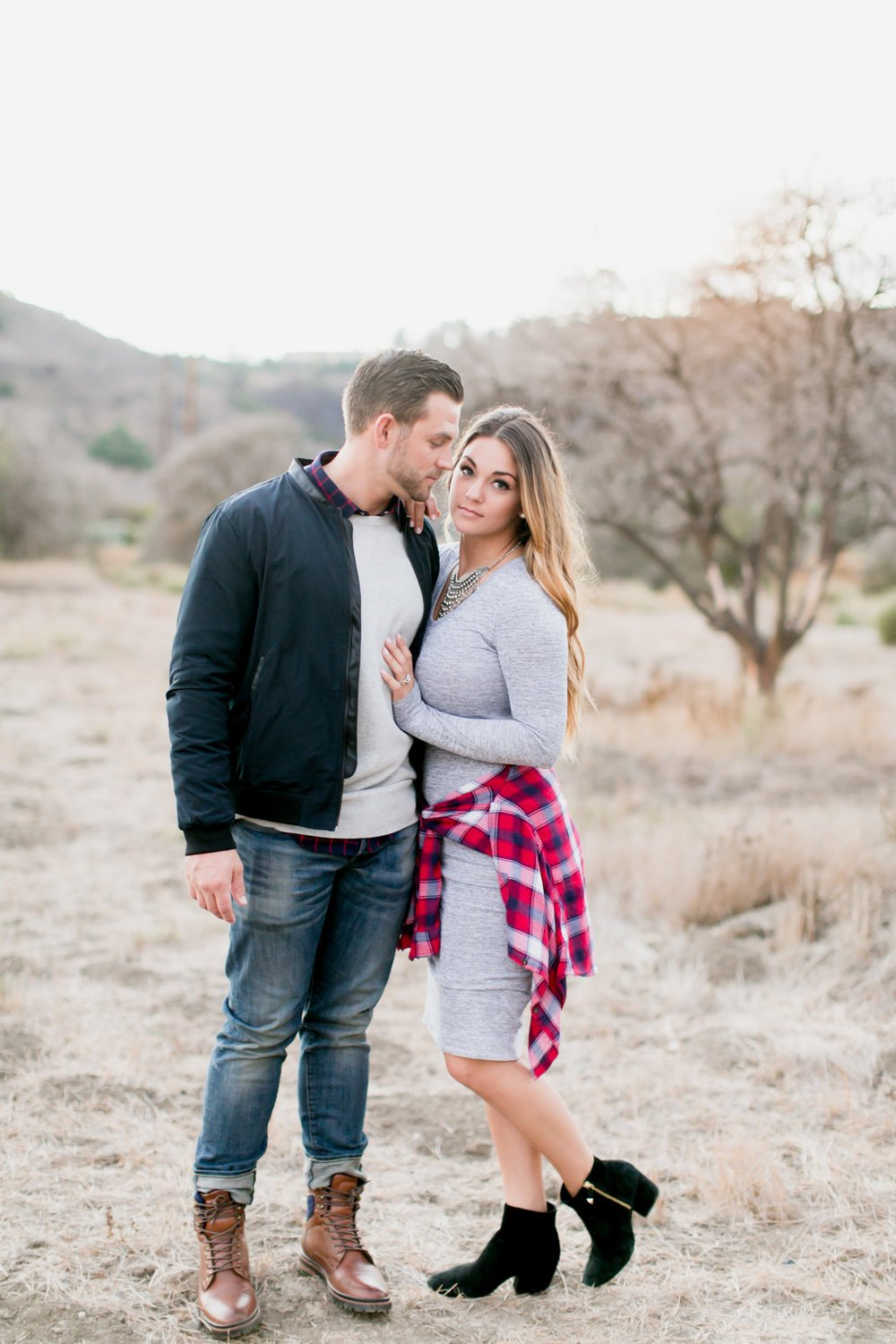 Engaged couple cuddles during outdoor engagement session in a field in San Juan Capistrano, California with Long Beach wedding photographer Lovisa Photo.