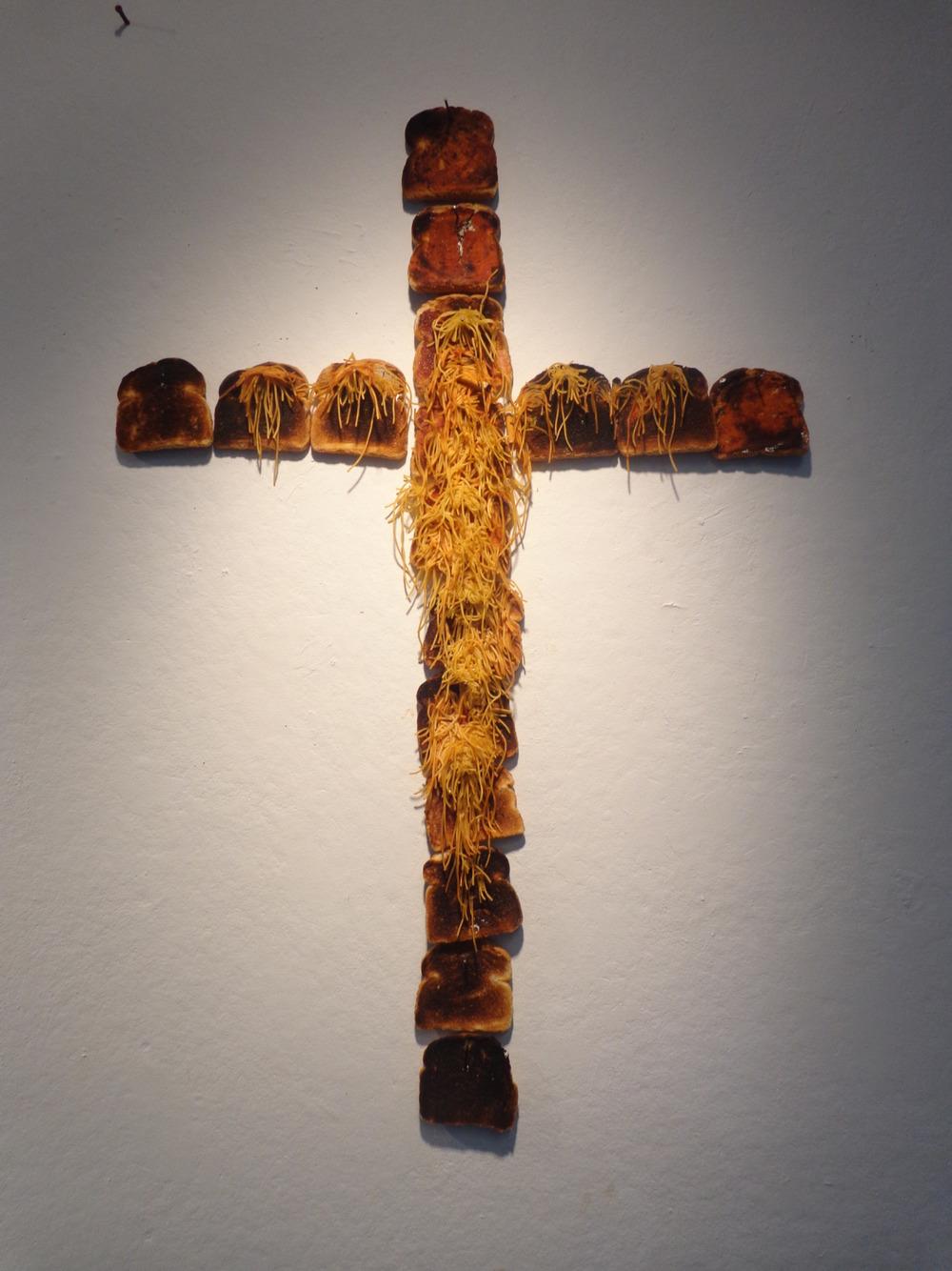 """Spaghetti Jesus.  Spaghetti, White Bread, Tomato Sauce, Wine,Cigarette. 55"""" x 35"""" x .5"""".2013."""