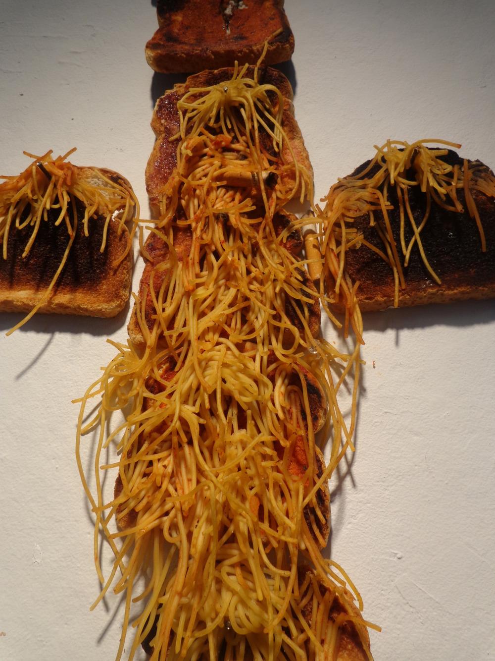 Spaghetti Jesus (detail). Spaghetti, Bread, Tomato Sauce, Wine, A Cigarette. 2013.