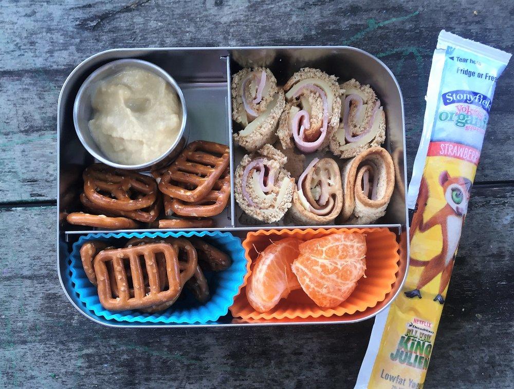 Hummus and pretzels, clementine, turkey/cheese/mustard roll-up, and yogurt tube