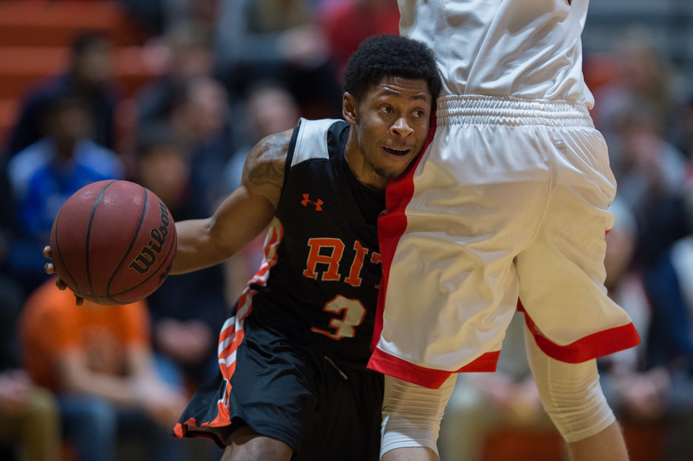 RIT Tigers AJ Horde, 3, collides with RPI Engineers Marcus Giese, 42, while making a dash to the rim during the 1st half in the Clark Gym on the Rochester Institute of Technology campus in Henrietta, N.Y. on Jan. 29, 2016. The Tigers went on to defeat the Engineers 65-57.