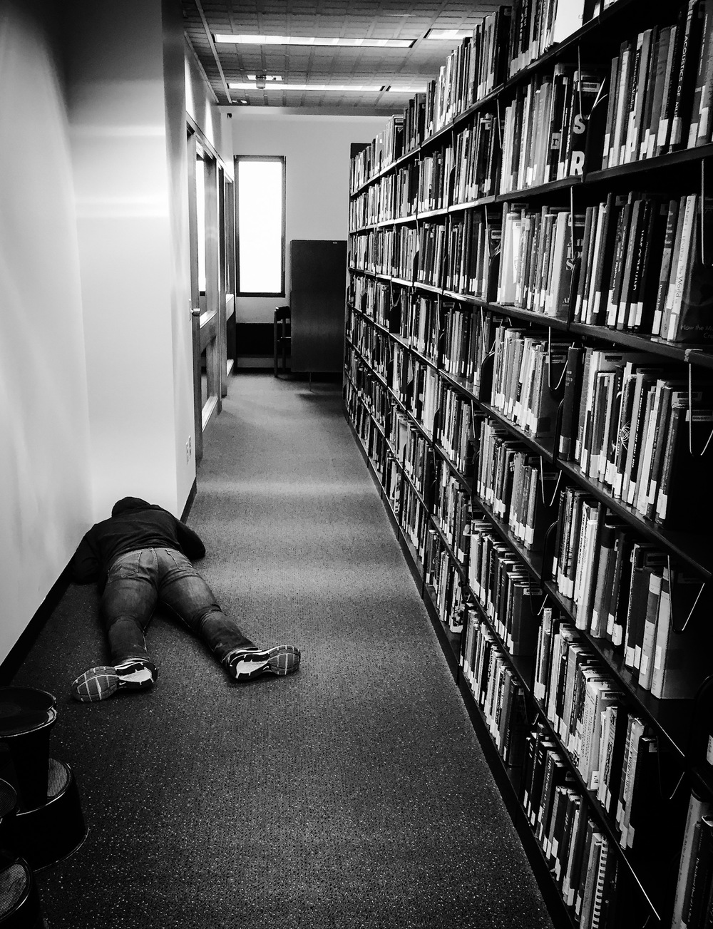 iPhone photo of a student sleeping at the Wallace Library on the RIT campus.