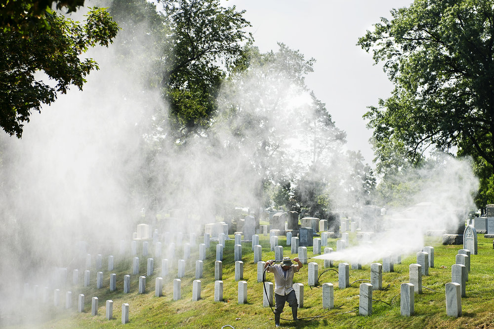 A worker uses a pressure washer to clean the tombstones at the Arlington National Cemetery in Arlington, VA, on July 17, 2017.