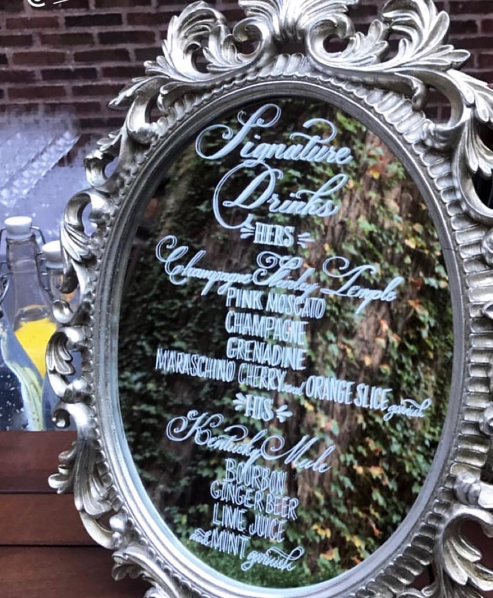 "9.5"" x 17"" Oval Mirror. Silver, metal, ornate frame. Perfect for a menu or signature drinks. $25 rental fee. 