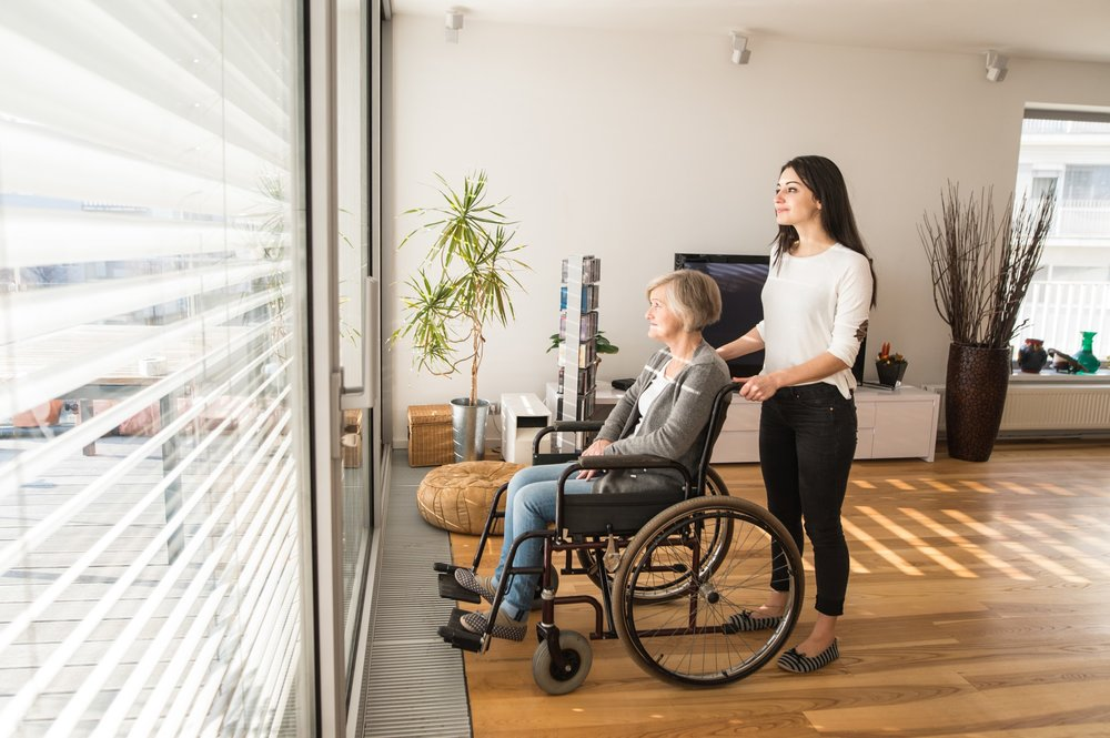 graphicstock-disabled-senior-woman-in-wheelchair-at-home-in-her-living-room-with-her-young-daughter-caring-for-her-looking-out-the-window_BuMnN_8MZ-SM.jpg