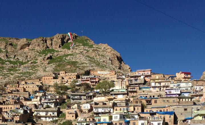 A Kurdish flag flies over hills in Kurdistan. Photo courtesy of Dilshad Qadir.
