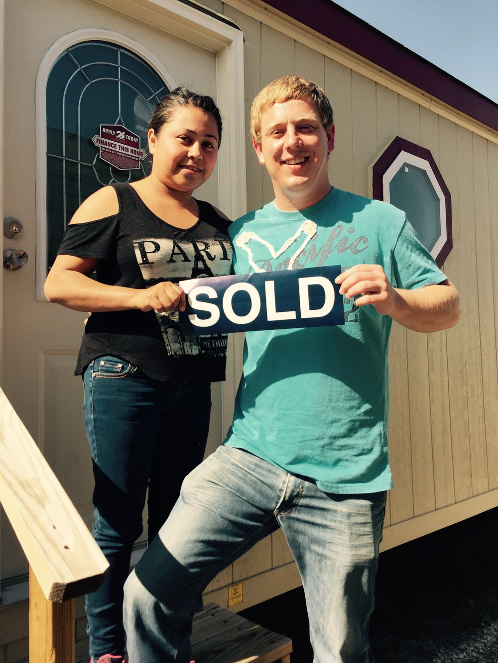Man and Woman Happily hold SOLD sign