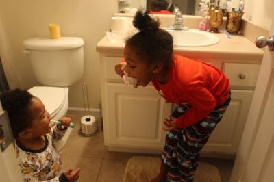 Winnie schooling IV on the art of teeth brushing.