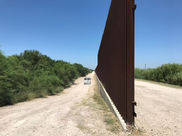 A Border Patrol vehicle travels down the road past the wall. This is approximately one mile from the actual border with Mexico.