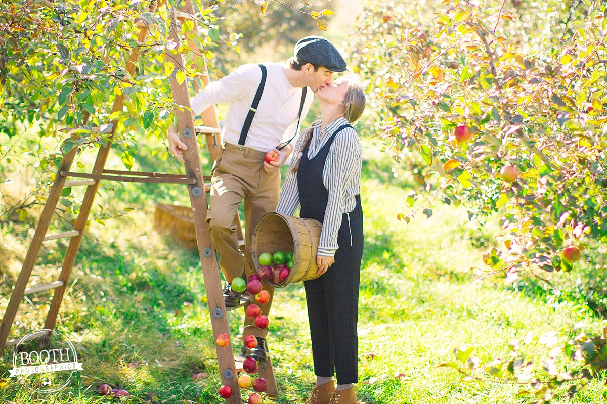 Couple kissing and holding apples at the Door Creek Orchard in Madison