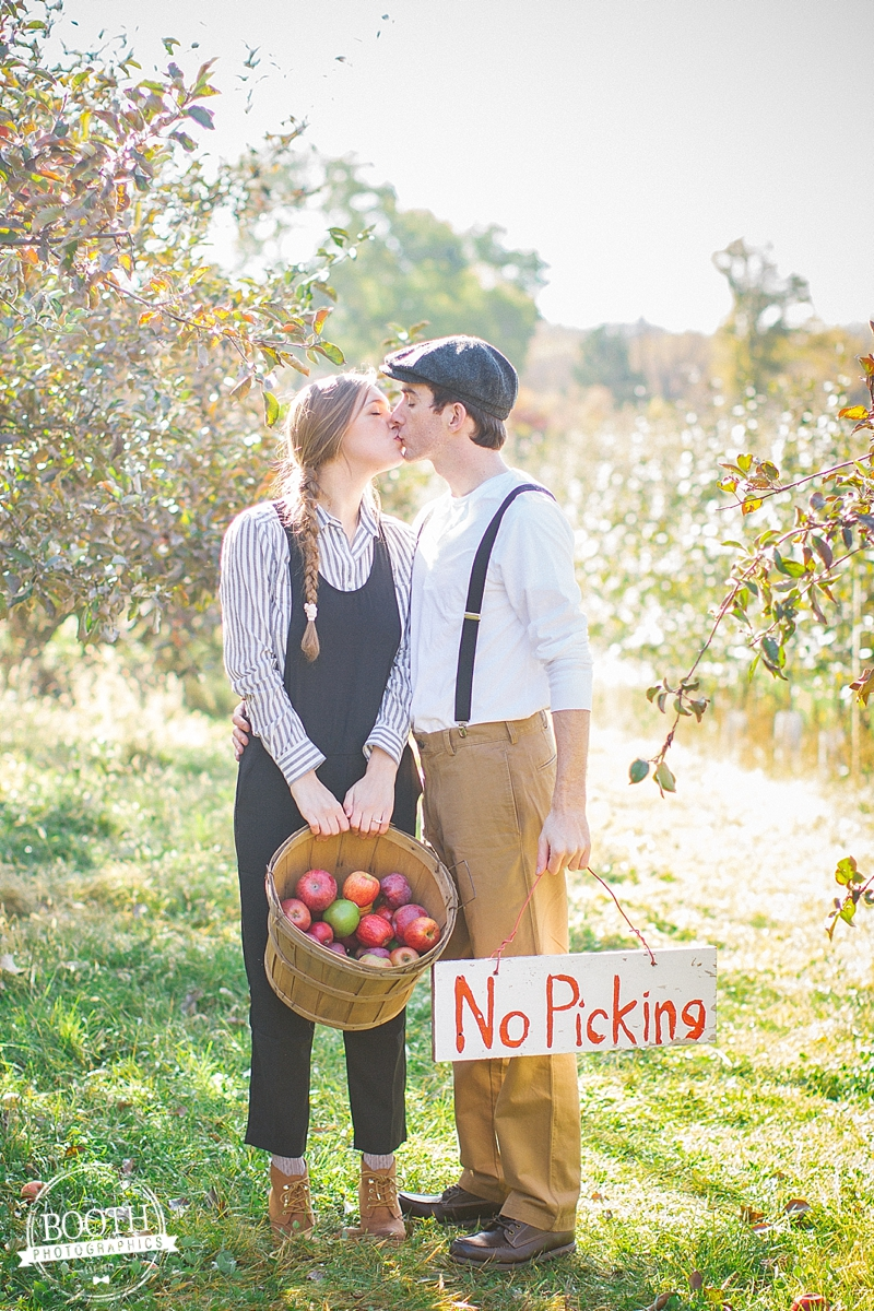 couple holding apples and kissing in a Madison Wisconsin orchard