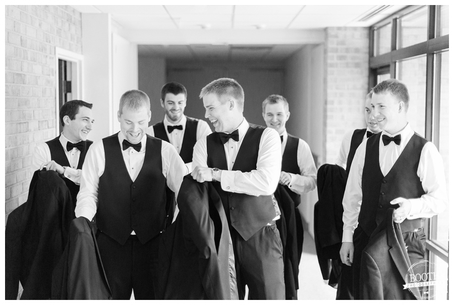 groomsmen getting ready for a wedding and putting suit coats on