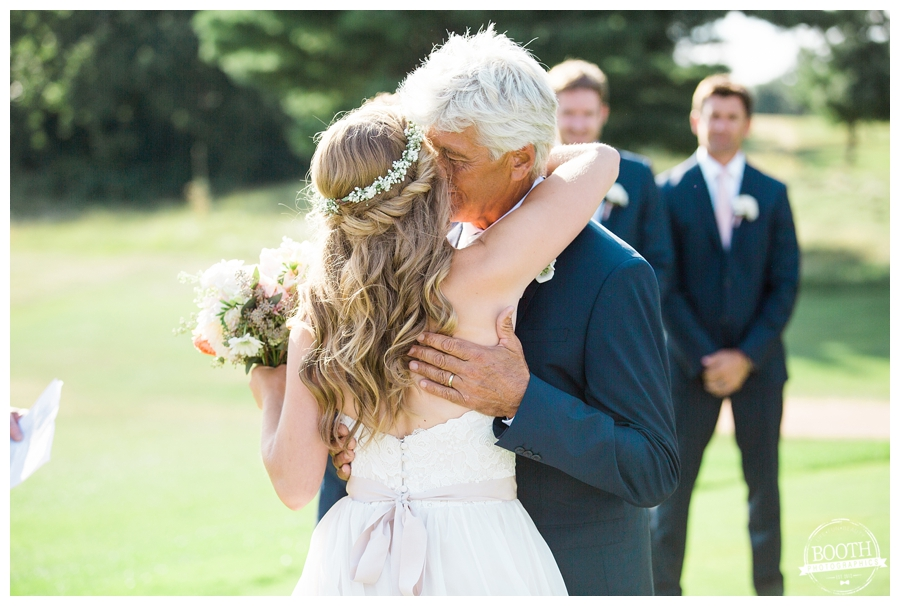 bride and her father hugging at the end of the aisle at an outdoor wedding ceremony