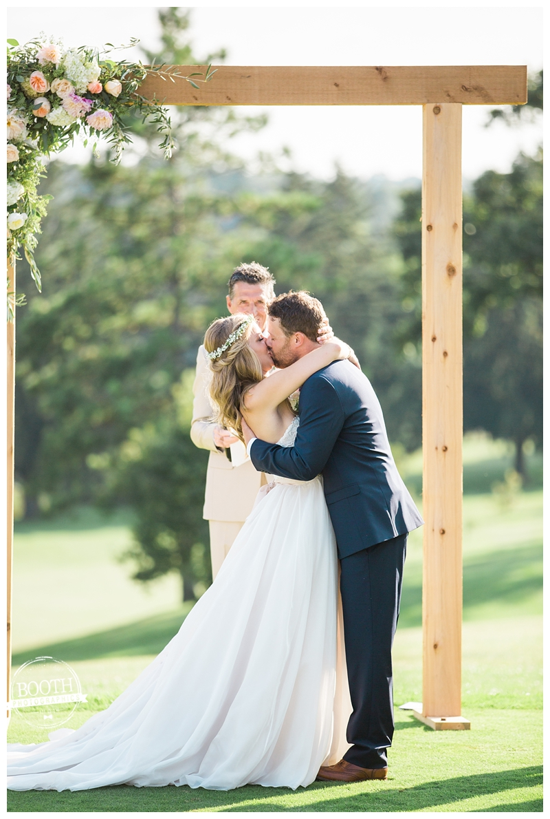 bride and groom kissing at the end of their outdoor wedding ceremony