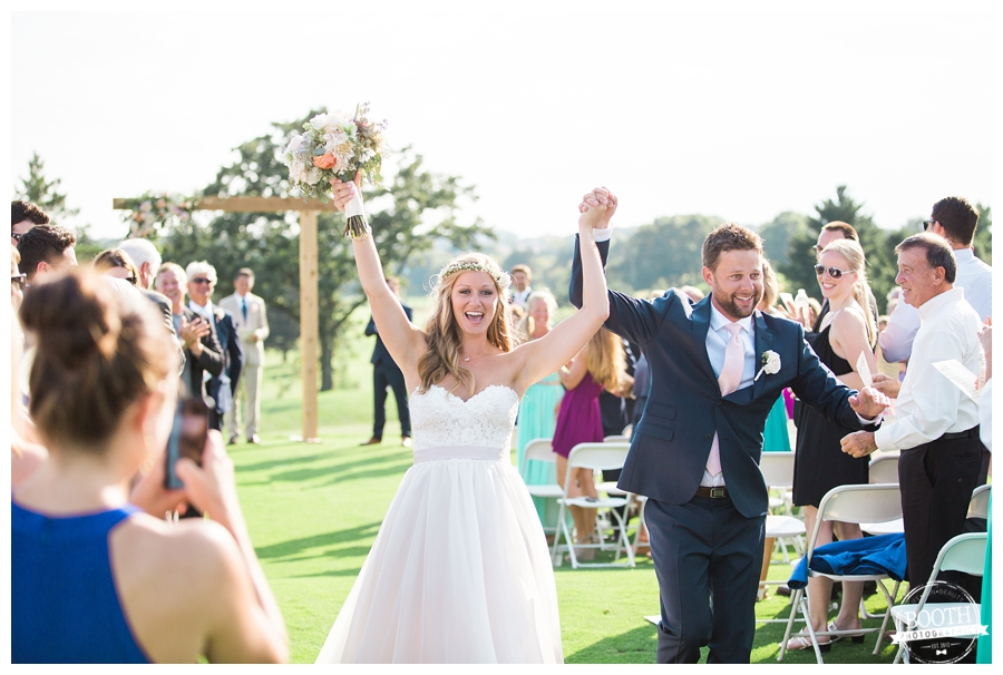 bride and groom cheering as they walk down the aisle together after their wedding ceremony