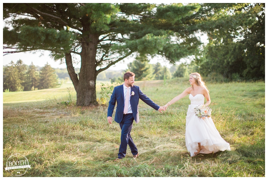 couple walking through a field together at their outdoor wedding