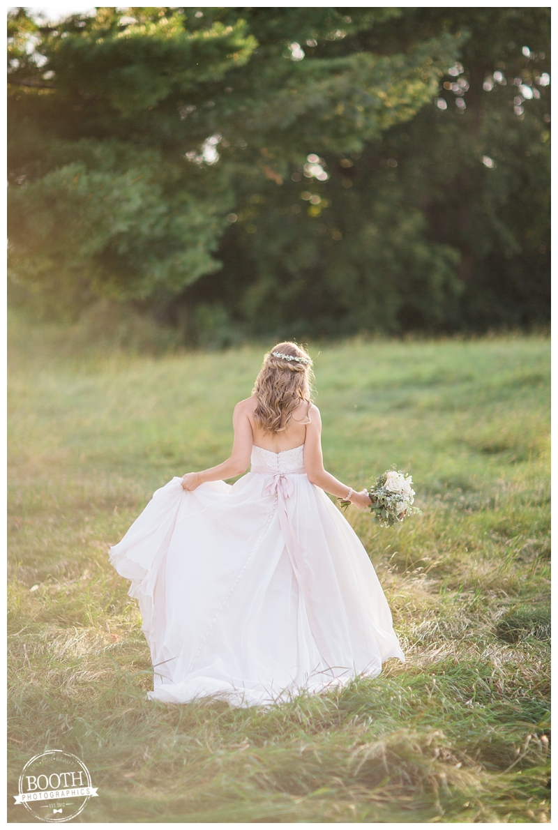 beautiful boho bride walking through a sunny field at her outdoor Wisconsin wedding