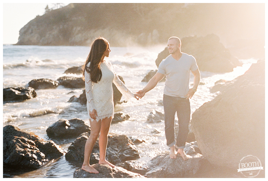 Couple standing on the rocks in the pacific ocean during their San Francisco Muir Beach engagement session