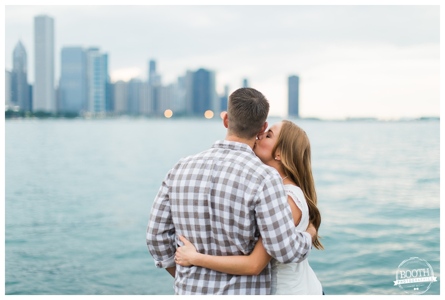 cute engaged couple  in Chicago standing at the edge of Lake Michigan looking out at the water