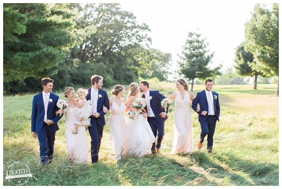 bridal party walking together in a grassy Wisconsin field